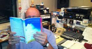 Mystery man reading at his desk (you know him as the morning voice of ncpr).