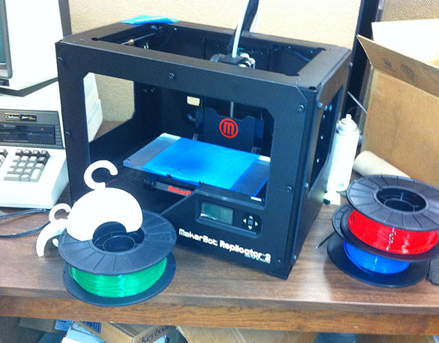 "The 3-D printer in Clarkson's engineering lab. The spools hold the plastic-like coil that is fed into and melted by the ""printer"" before being squirted onto the turquoise building surface. Photo: Ellen Rocco"