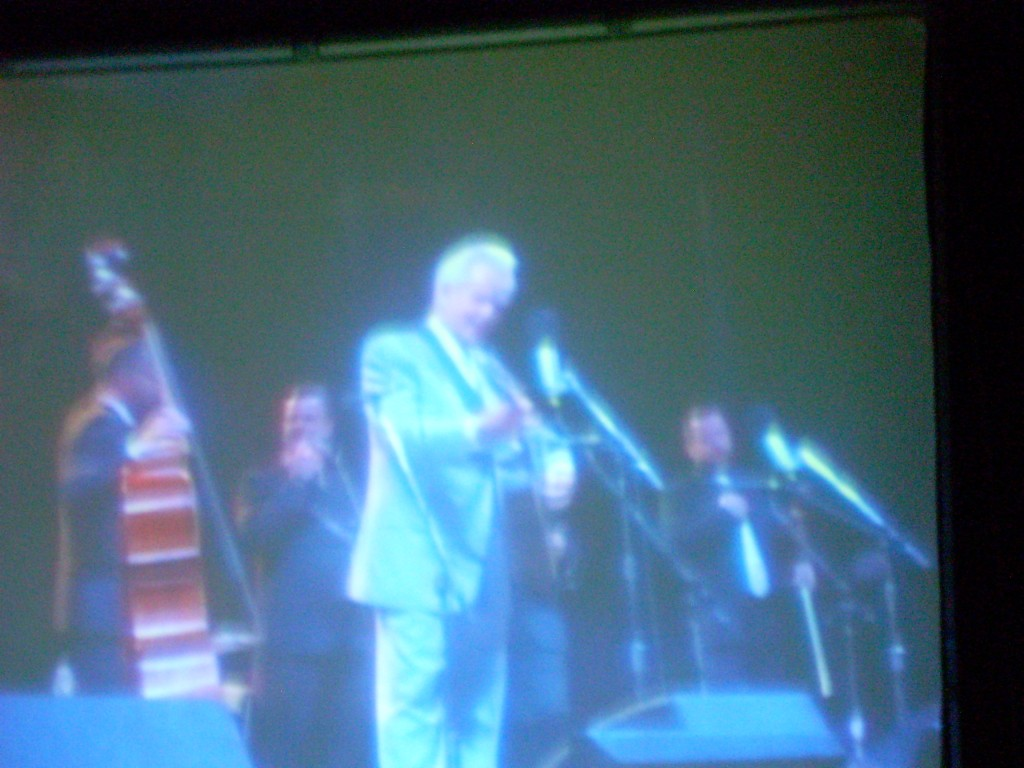 Greetings from the Grey Fox Bluegrass Festival in Oak Hill, NY... just south of Albany, in the foothills of the Catskill mountains.   This is Del McCoury (on the JumboTron).  Yes, the photo is 'backwards'.  I was standing backstage behind the JumboTron, so all images were reversed.  Del turns 75 this year, and the Grey Fox crowd LOVED celebrating his milestone!