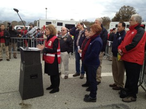 Red Cross CEO Gail McGovern speaks at a post-Sandy press conference on Staten Island with emergency response vehicles as backdrops. Relief workers were angered that the vehicles were diverted for public relations purposes. (Via ProPublica: Catherine Barde/American Red Cross via Flickr)