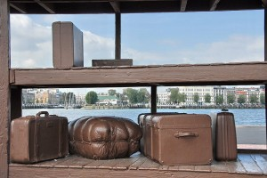 This Rotterdamn scup[ture,  'Lost Luggage Depot' was made by the Canadian plastic artist Jeff Wall (1946-). It is made of cast iron and symbolizes the goodbye of the many emigrants to their former lives. Image: Rotterdam 'Kop van Zuid', Creative Commons