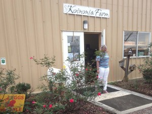 Roses bloom as Beria steps outside of the Koinonia store.