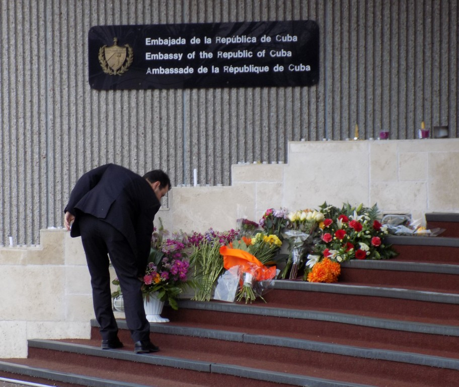 Flowers for Fidel, candles for Castro.  An employee adds to the informal tributes to Fidel Castro that have appeared on the steps of the Cuban Embassy in Ottawa.  Photo: James Morgan