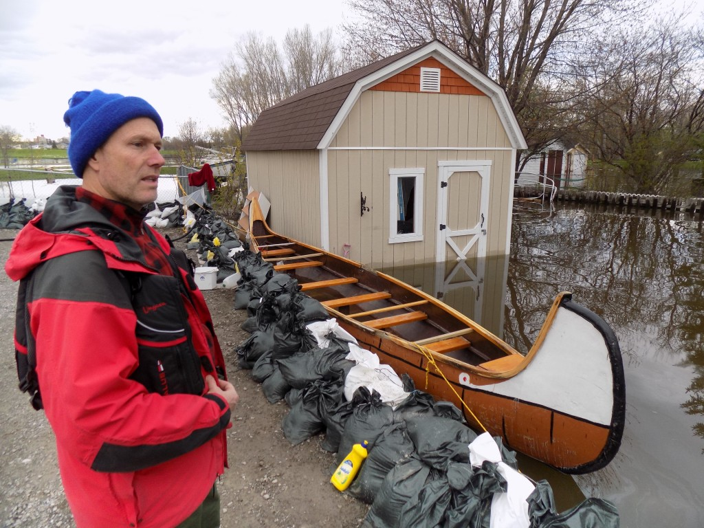 John Savage and one of the Voyageur-style canoes used to deliver sandbags in his neighborhood.  Photo: James Morgan