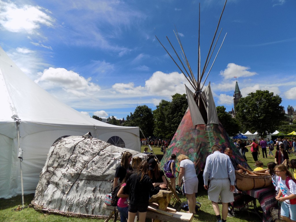 A tepee and wigwam in Major's Hill Park on National Aboriginal Day in Ottawa.  The Parliament Buildings stand in the background.  Both locations are on land that was not formally surrendered by the Algonquin people.  Photo: James Morgan