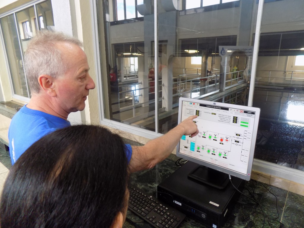 A City of Ottawa employee demonstrates the SCADA system that is used to monitor plant operations.  Filtration pools are located behind the window.  Photo: James Morgan