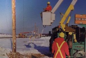 """Ontario utility crews rebuilding a line destroyed by the ice storm.  Photo from """"To The Rescue: A Commemorative Magazine Dedicated to All Those Who Battled the Darkness and Won.""""  Ontario Hydro, 1998."""