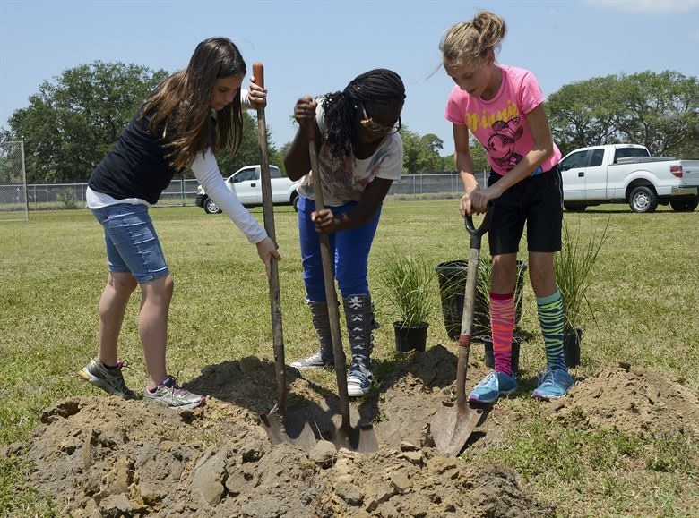 Tinker Elementary School 5th graders shovel dirt while planting trees around the school playground during an Arbor Day ceremony. Photo: Senior Airman Shandresha Mitchell, US Air Force