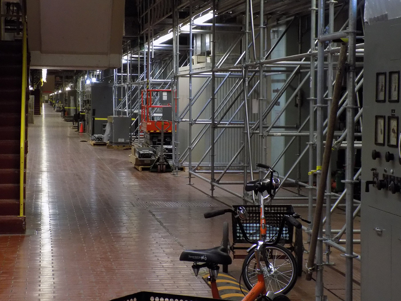 The row of governor control units for each generator. The scaffolding is a temporary measure while work is done to reduce concrete expansion. The tricycle is one of many ways plant employees travel around the large facility.  This photo was taken looking south from unit 1.  Photo: James Morgan