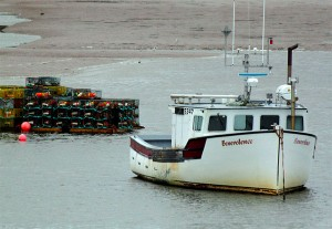 "The Canadian lobster boat ""Benevolence"" and a stack of traps at low tide. Lobster prices are also ebbing. Photo: Karen Morris, Creative Commons, some rights reserved"
