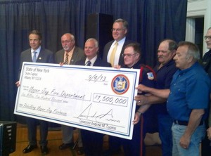 Gov. Cuomo presents symbolic  $1.5 million check to Upper Jay Fire Department. Photo: Brian Mann