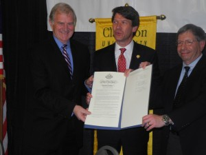 From left, Clarkson University President Tony Collins, Empire State Development President Ken Adams and Trudeau Institute President and CEO Ron Goldfarb hold up a copy of a memorandum of understanding committing the three to a $35 million biotech partnership. The deal was signed Wednesday at the Lake Placid Conference Center. (Photo:  Chris Knight, Adirondack Daily Enterprise)