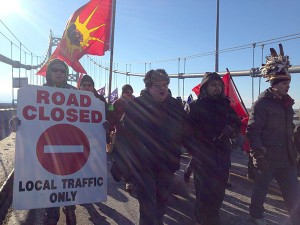 """Mohawks and supporters crossing the old Cornwall bridge during the """"Idle No More"""" march in January 2013. Photo: David Sommerstein"""