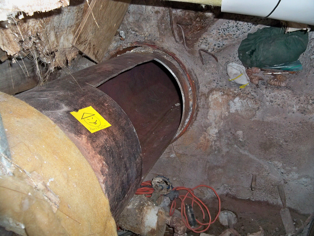 """Step Four: Cutting through a steam pipe to create an escape tunnel. They left behind a taunting note (yellow post-it says """"Have a Nice Day"""")."""